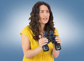Serious casual young woman holding binoculars — Stock Photo