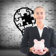 Composite image of businesswoman holding piggy bank — Stock Photo