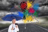 Happy mature businessman holding umbrella — Stock Photo