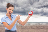 Composite image of businesswoman indicating alarm clock — Stock Photo