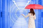 Composite image of businesswoman holding umbrella — Stock Photo