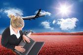 Composite image of businesswoman using laptop — Stock Photo