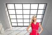 Composite image of elegant blonde standing hands on hips — Stock Photo
