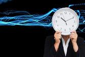 Imagen compuesta de empresaria en traje sosteniendo un reloj — Foto de Stock