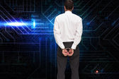 Rear view of young businessman wearing handcuffs — Stock Photo