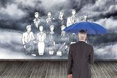 Composite image of businessman holding umbrella — Stock Photo