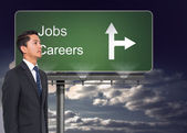 Composite image of signpost showing the direction of jobs and careers with sky — Stock Photo