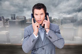 Angry businessman tangle up in phone wires — Stock Photo
