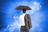 Composite image of businessman standing back to camera holding umbrella — 图库照片