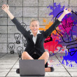 Composite image of businesswoman sitting in front of laptop with arms up — Stockfoto #38502551