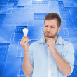 Stock Photo: Sceptical model holding bulb