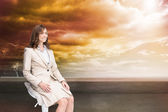 Composite image of smiling businesswoman sitting — Stock Photo