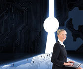 Composite image of businesswoman using laptop — Stock Photo