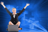 Composite image of businesswoman sitting in front of laptop — Stock Photo