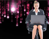 Composite image of businesswoman sitting on swivel chair with laptop — 图库照片