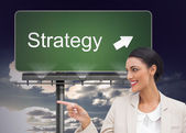 Composite image of smiling businesswoman pointing — Stock Photo