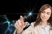 Composite image of businesswoman touching invisible screen — Stock Photo