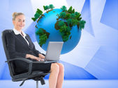 Composite image of businesswoman sitting in swivel chair with laptop — Stock Photo