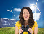 Casual young woman holding binoculars — Stock Photo