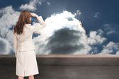 Composite image of rear view of young businesswoman looking away — Stock Photo