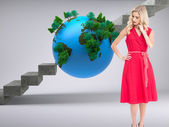 Blonde standing hand on hip in red dress — Stock Photo