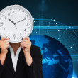 Composite image of businesswoman in suit holding a clock — Stock Photo #38512493