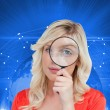 Stock Photo: Fair-haired woman looking through a magnifying glass
