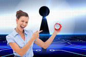 Businesswoman indicating alarm clock with finger — Stock Photo