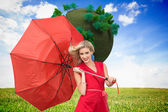 Smiling blonde holding umbrella — Stock Photo