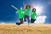 Three enviromental activists jumping and smiling — Stock Photo