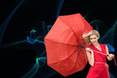 Composite image of smiling blonde holding umbrella — Stock Photo