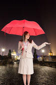 Attractive businesswoman holding red umbrella — Stock Photo