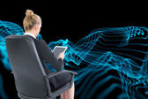 Composite image of businesswoman sitting on swivel chair with tablet — Stock Photo