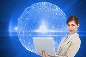 Composite image of confident young businesswoman with laptop — Foto de Stock