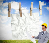 Smiling architect with hard hat looking at plans — Stock Photo