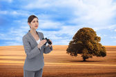 Composite image of curious young businesswoman with binoculars — Stock Photo