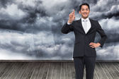 Composite image of smiling asian businessman pointing — Stock fotografie