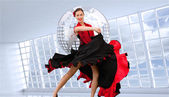 Dancing woman in a red and black dress — Stock Photo