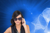 Serious elegant brunette wearing sunglasses on the phone — Stock Photo