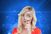 Fair-haired woman looking through a magnifying glass — Stock Photo