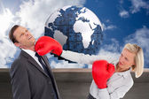 Composite image of businesswoman hitting colleague with her boxi — Stock Photo