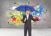Businessman holding umbrella — Stock Photo