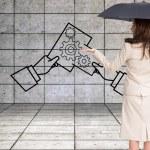 Composite image of elegant businesswoman holding black umbrella — Stock Photo