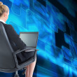 Stock Photo: Blonde businesswomsitting on swivel chair with laptop