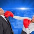 Stock Photo: Businesswoman hitting colleague with her boxing gloves