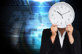 Composite image of businesswoman in suit holding a clock — Photo