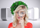 Woman looking through a magnifying glass — Stock Photo
