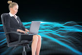 Blonde businesswoman sitting on swivel chair with laptop — Stock Photo
