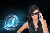 Composite image of serious elegant brunette wearing sunglasses — Stock Photo