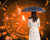 Composite image of rear view of classy businesswoman holding umbrella — Stock Photo